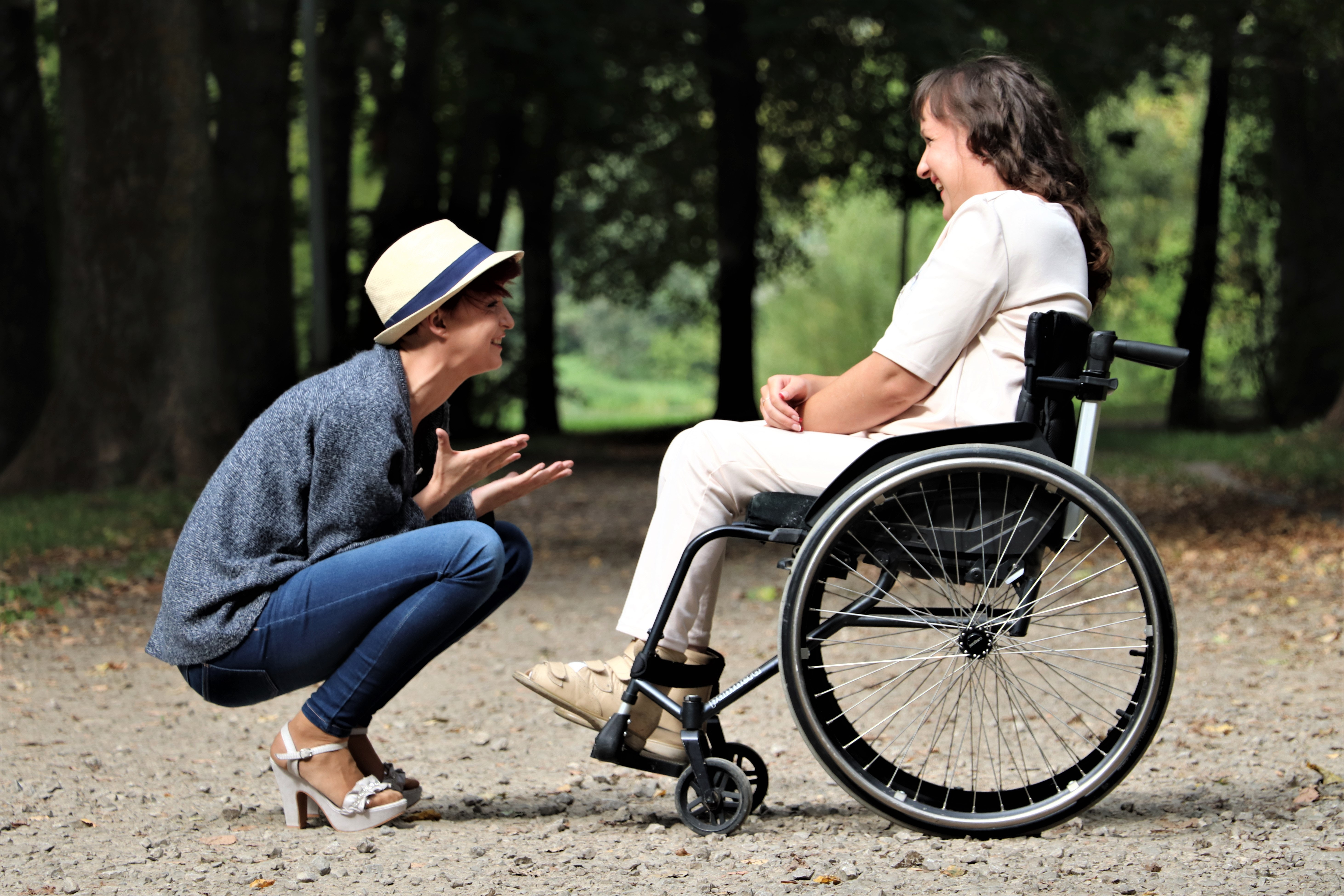 A health care assistant and an adult with disability are having fun at a park