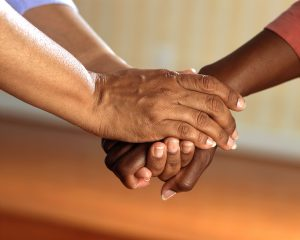 A person and a care giver are holding hand intimately