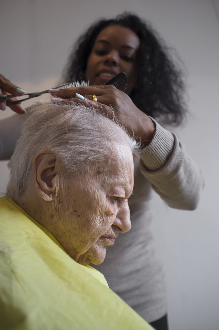 A health care assistant cutting hair to elderly woman