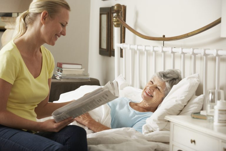 A Health Care Assistant Reading Newspaper To Senior Female Elderly In Bed At Home