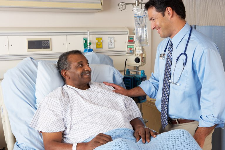 Doctor Visiting Senior Male Patient On Ward