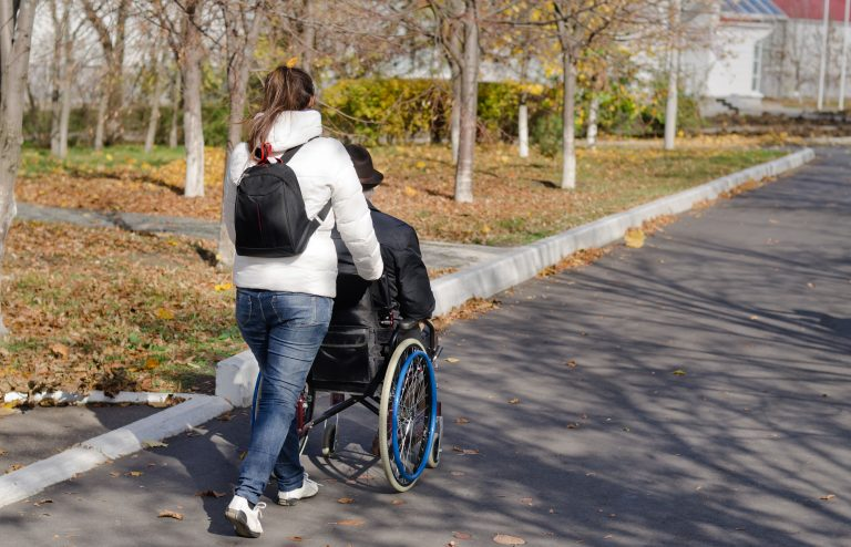 Female Health Care Assistant taking a disabled man in a wheelchair for a walk along the street